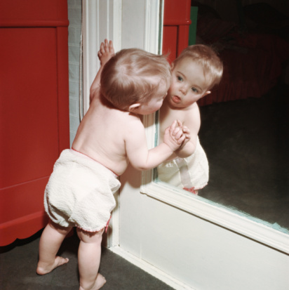 Baby looking at reflection in mirror