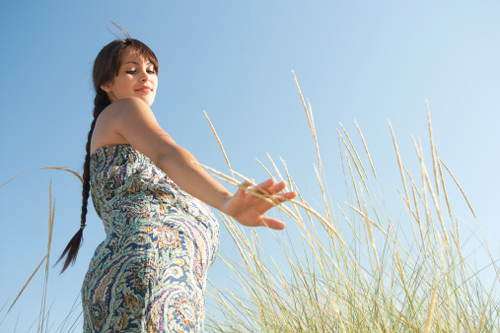 Pregnant woman walking in wheat field