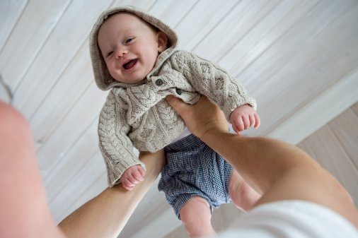 Man lifting baby boy (4-6 months) upward, smiling, close-up