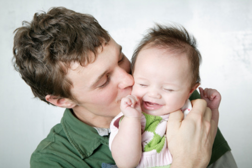 Father kissing baby girl (3-6 months) on cheek, baby laughing