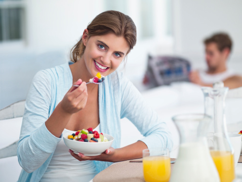 Young woman eating fruit salad with boyfriend in the background