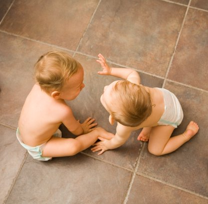 Baby girl & boy (9-12 months) playing on floor, elevated view
