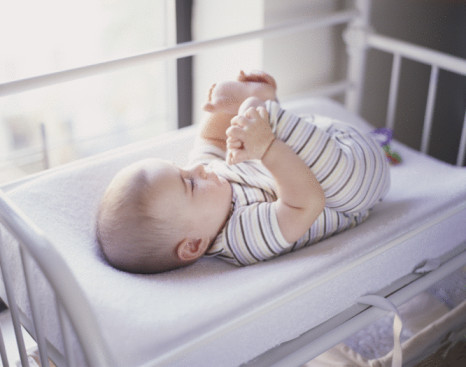Baby Playing with Own Feet While Lying on Changing Table