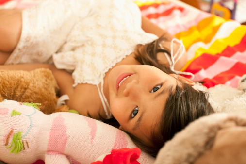 Young girl lying on bed with toys.