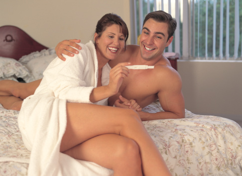 portrait of a happy young couple on the bed with a pregnancy test kit