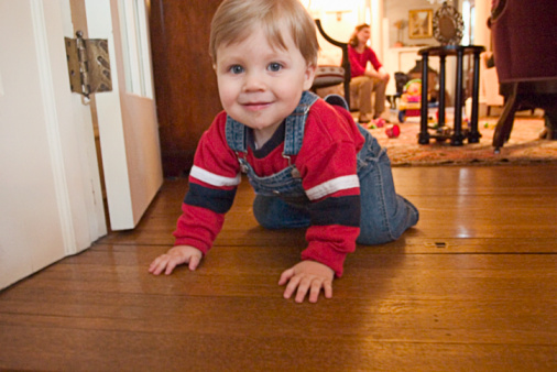 Toddler boy crawling on wooden floor, mother in background.