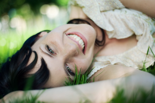 Young woman lies in grass laughing merrily