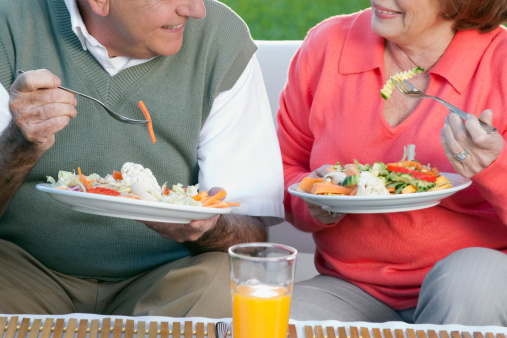 Couple eating salad in a lawn