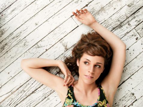 Young woman lying on hardwood floor