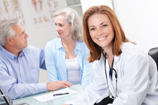 Smiling Doctor at Desk Meeting With Senior Adult Couple