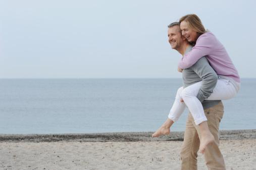 Man carrying girlfriend on beach