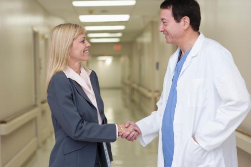 Businesswoman shaking hands with doctor in hospital corridor