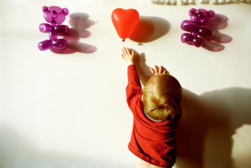Boy reaching for heart-shaped balloon