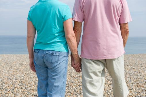 Elderly couple walking on a shingle beach holding hands