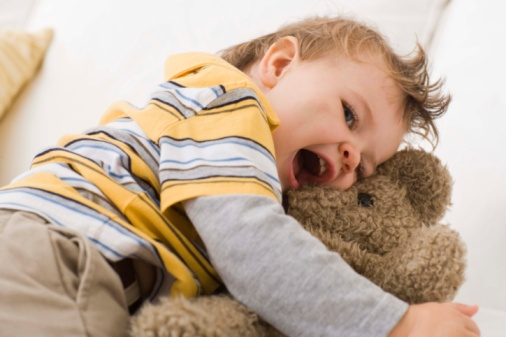 Toddler hugging teddy bear