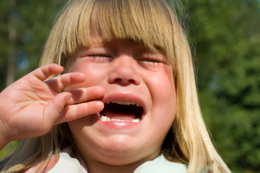 3 year old white caucasian girl crying and holding her hand to her face.
