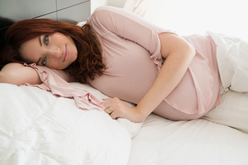 Pregnant Hispanic woman laying in bed